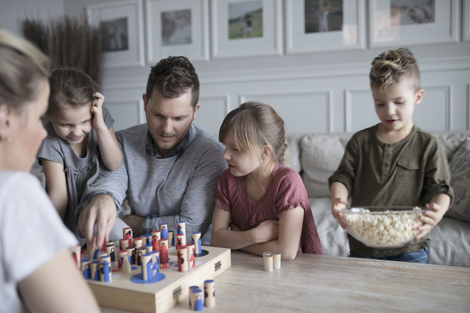 Young family playing game and eating popcorn in living room