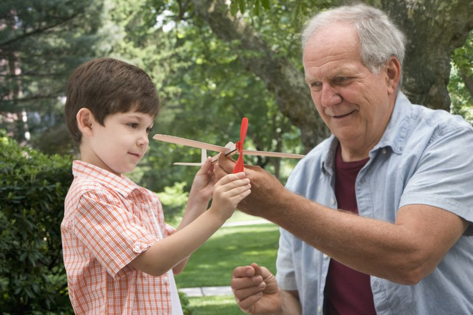 Grandfather and grandson fly a rubber band powered airplane.