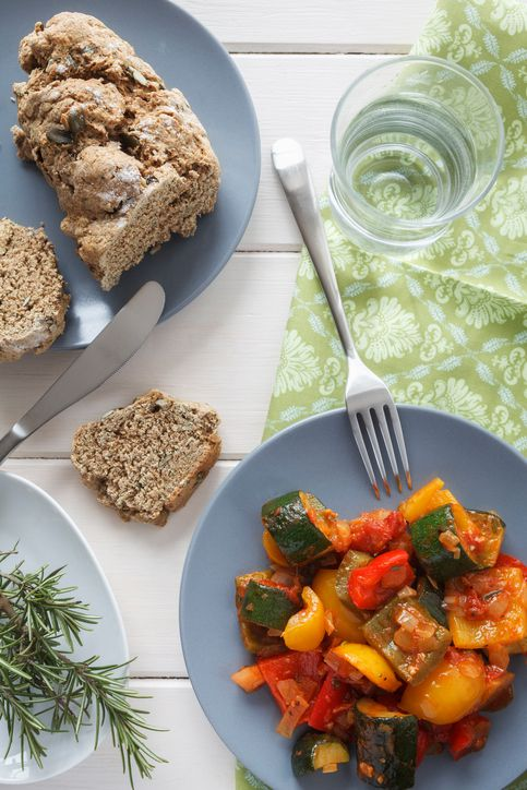 Ratatouille on plate besides bread slice and rosemary on table stock photo