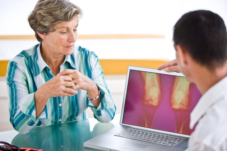 Doctor explains x-ray evidence of knee osteoarthritis to patient.