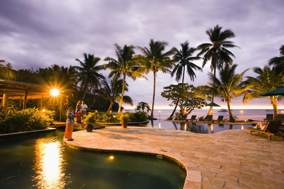 Patio next to an ocean beach with palm trees and a sunset.