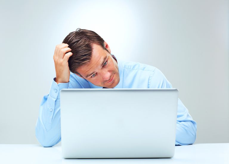 Confused man in front of laptop scratcing his head