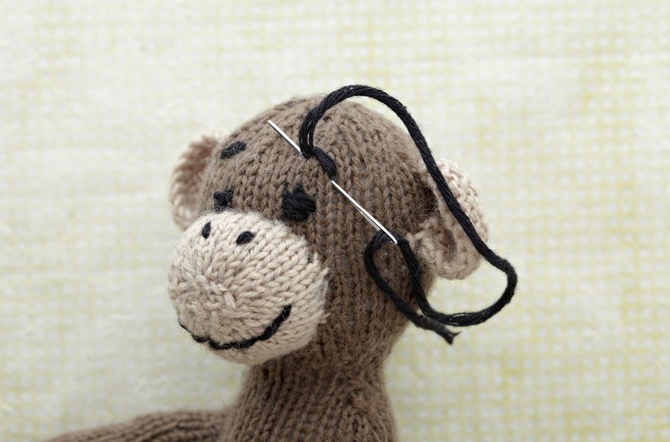 Eyebrow being sewn on face of knitted toy monkey, close-up