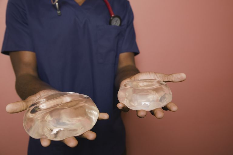 African doctor holding breast implants