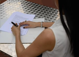 A picture of a woman signing a contract