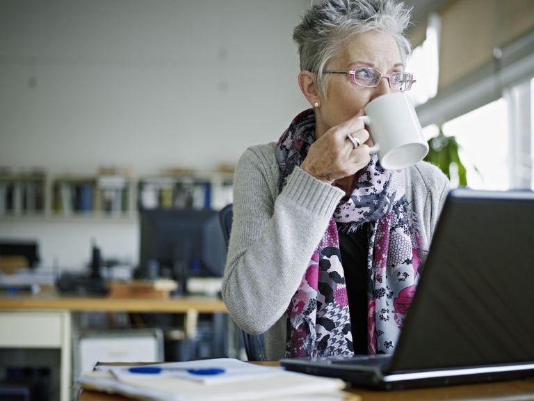 Businesswoman sitting in office drinking c...