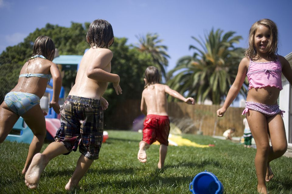 Kids in bathing suits running in backyard