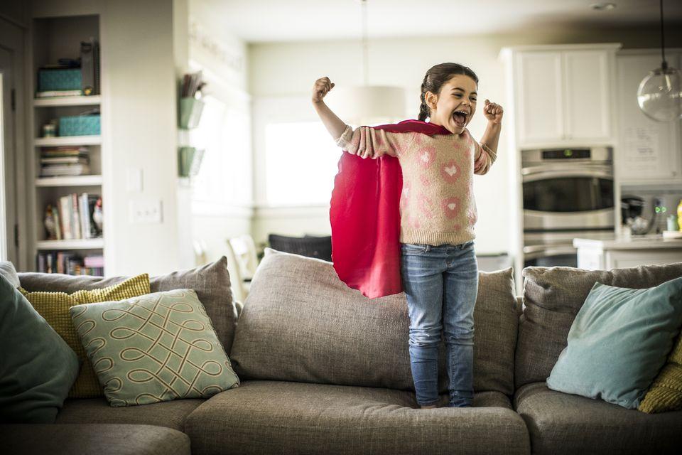 Girl (7yrs) wearing superhero cape, indoors