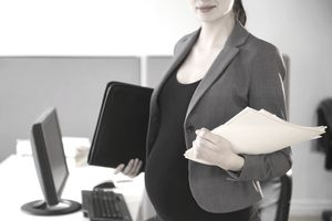 Pregnant caucasian businesswoman working in office