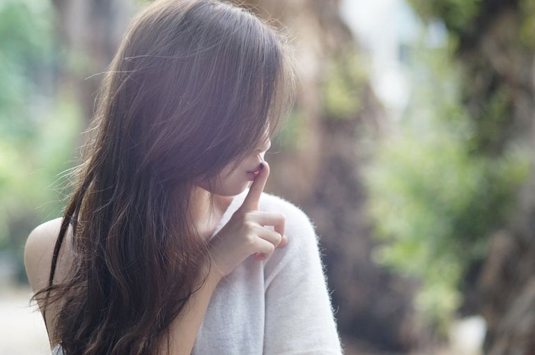 Woman holding her finger to her mouth sushing, silence on infertilty and miscarriage