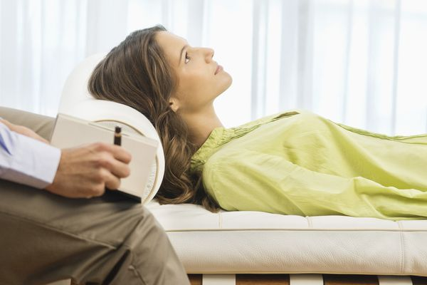 woman on couch while therapist takes notes