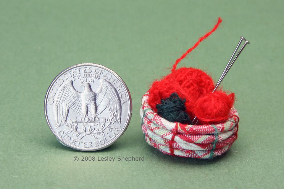 A 1:12 scale tartan coiled rag basket holds miniature knitting, needles and yarn.