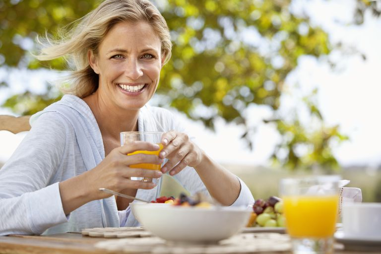 Smiling woman eating a healthy breakfast.