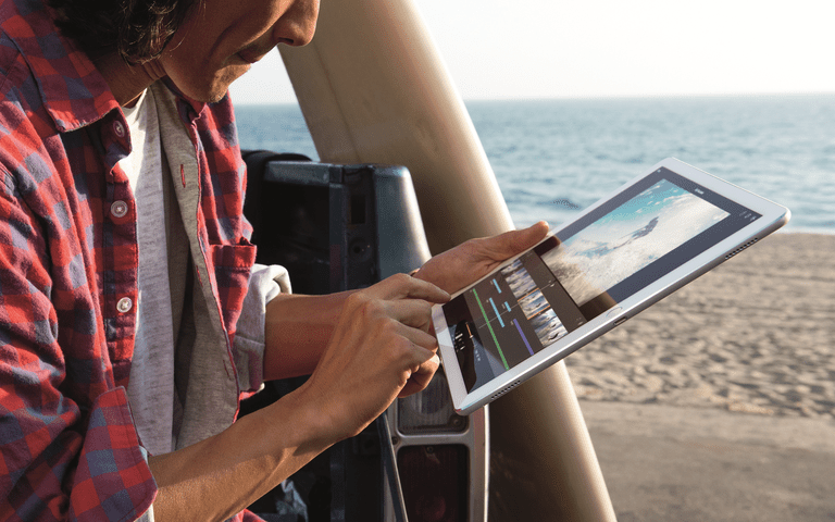 A man using an iPad Pro at the beach.