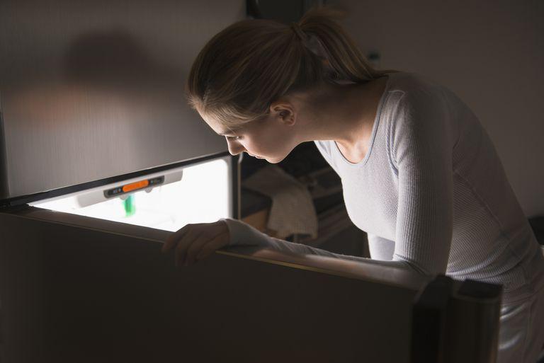 USA, New Jersey, Jersey City, Woman opening fridge at night