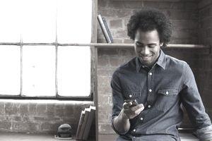 Man sitting on desk using smartphone