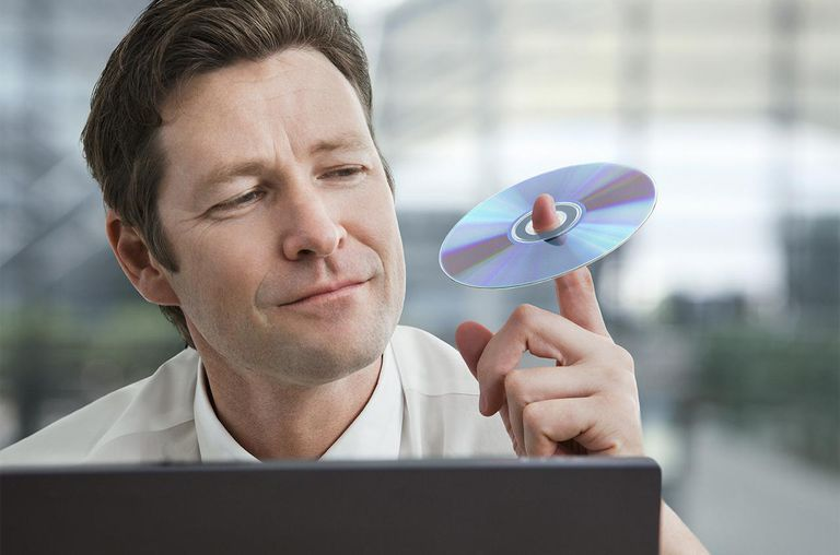 Businessman holding compact disc on his finger