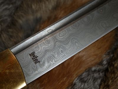 This is a modern forged Damascus steel blade with the characteristic wave pattern in the steel.