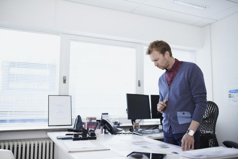 Man standing in his office looking at plans