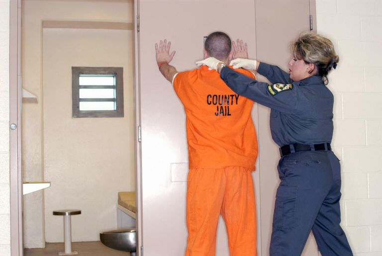 Corrections officer searching inmate