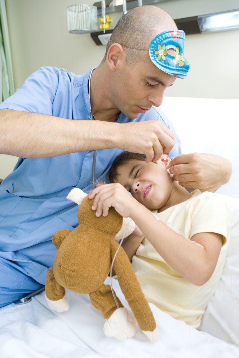 Doctor putting ear drops into a boy's ear.