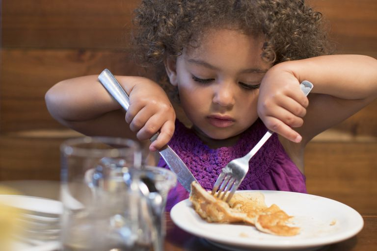 Young girl cutting her food with silverware