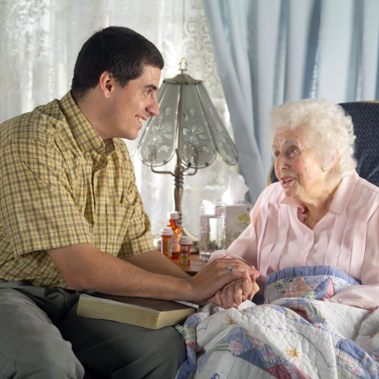 Man with bible on lap holding hands with senior woman, smiling