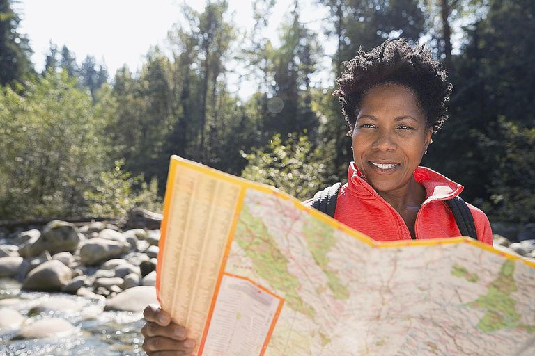 Woman looking at trail map in sunny woods