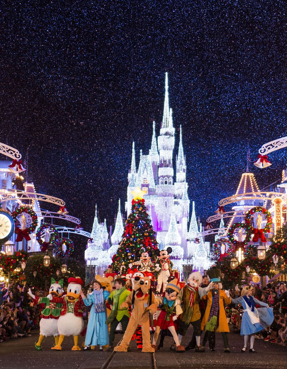 Winnie the Pooh and other Disney characters in holiday parade in front of Cinderella Castle at Magic Kingdom.