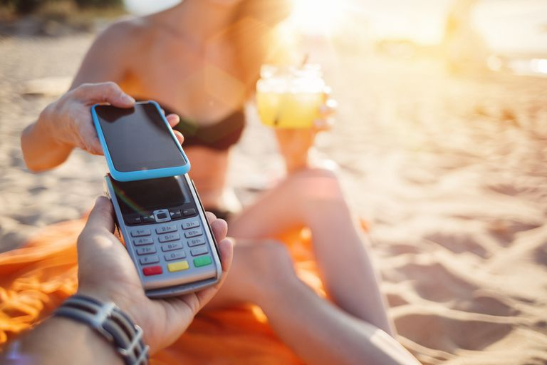woman paying for cocktail with smartphone on the beach