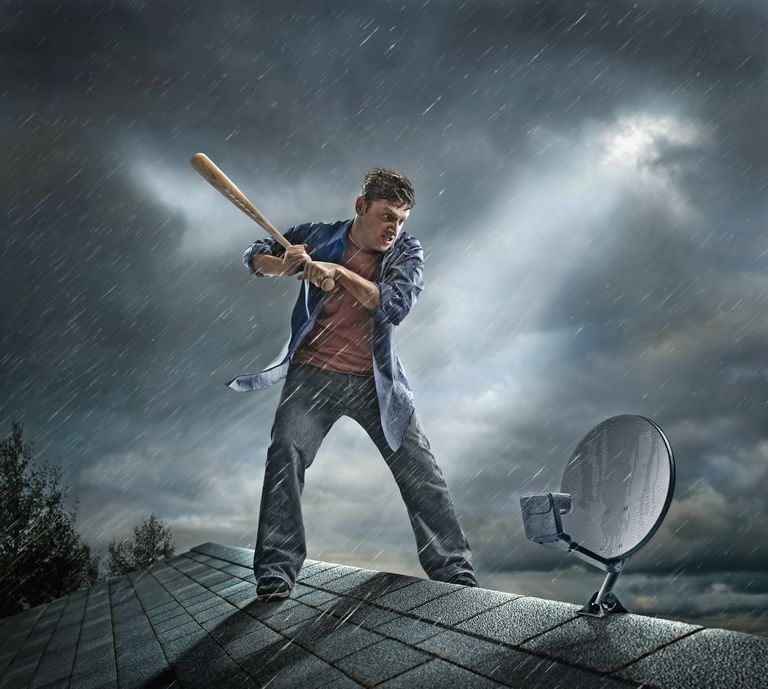 Stop losing satellite reception during a storm caucasian man swinging baseball bat at satellite dish on roof solutioingenieria Gallery