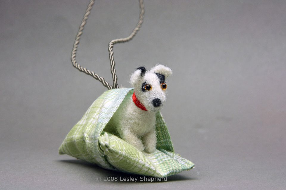 A dolls house scale Jack Russell Terrier tucked into the cushion on his dog bed.