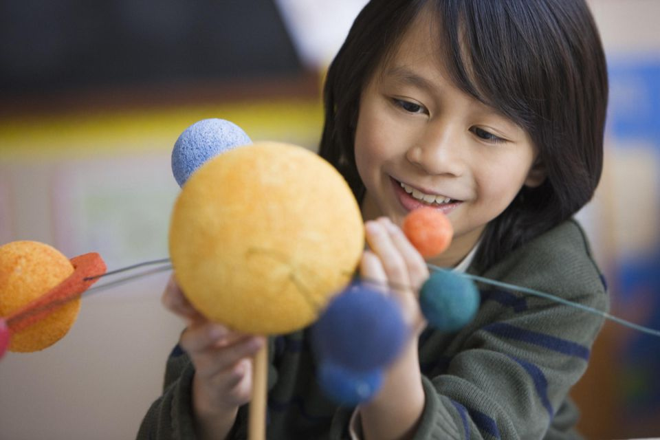 Pacific Islander boy making planet model in classroom
