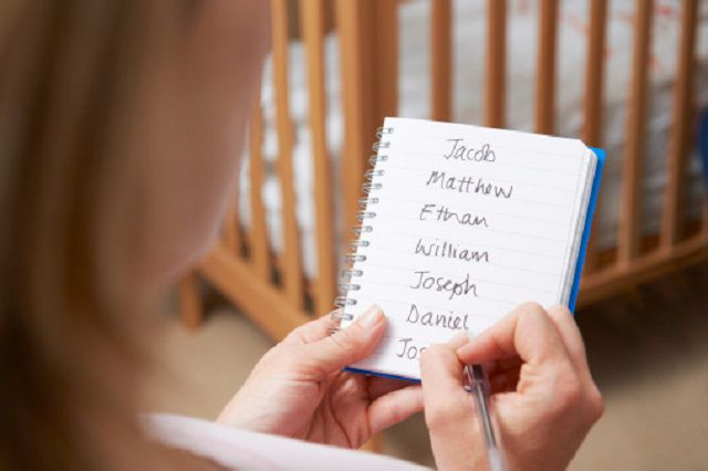 Woman Writing Possible Names For Baby Boy In Nursery