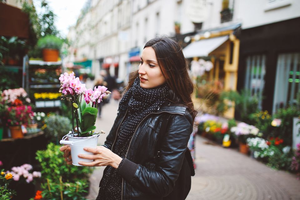 Young Parisian woman buying flowers on the streetmarket