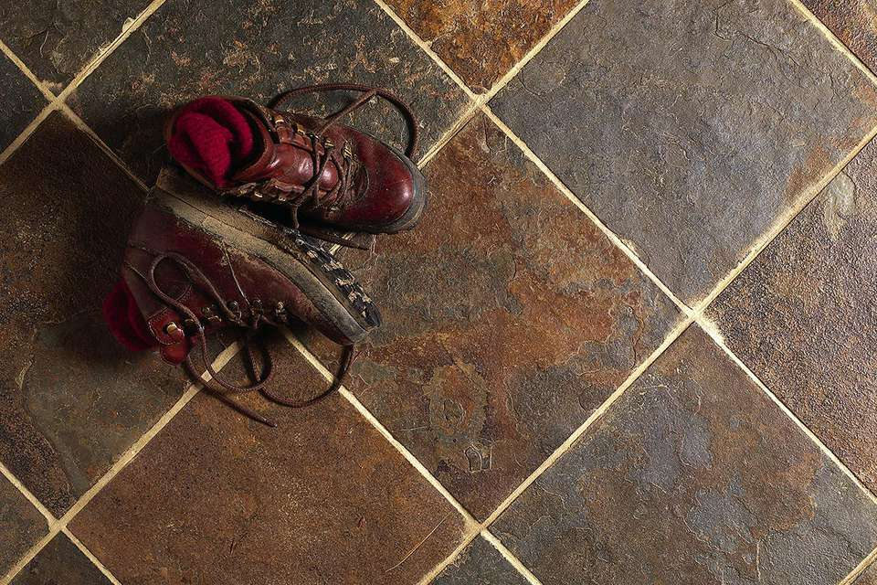 Dirty hiking boots on slate kitchen floor