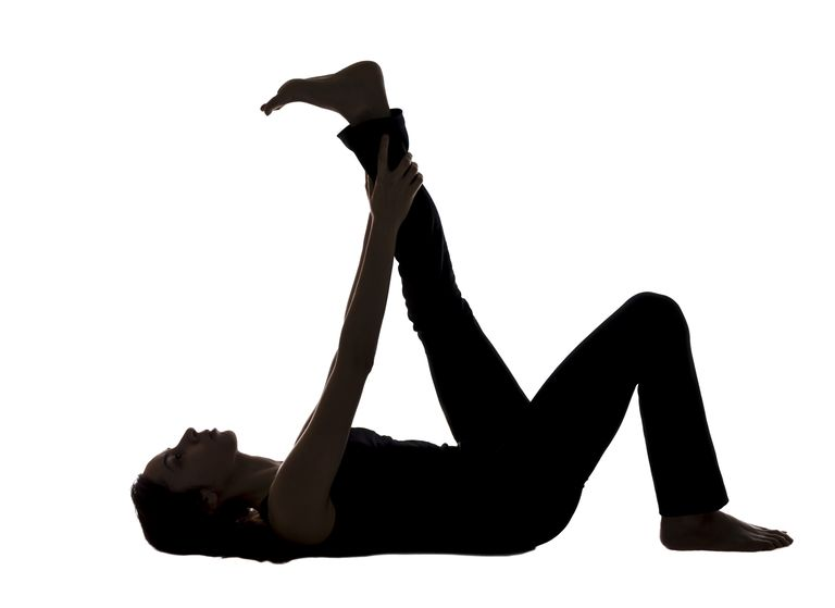 Silhouette of woman stretching hamstrings by grasping ankle of straight leg while lying on her back.