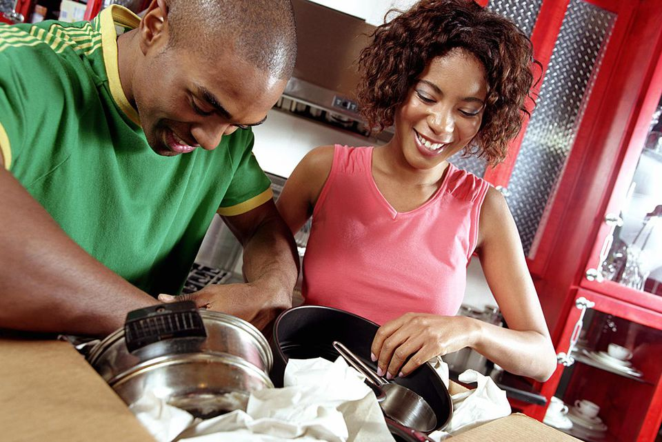 Young couple unpacking pots and pans, smiling
