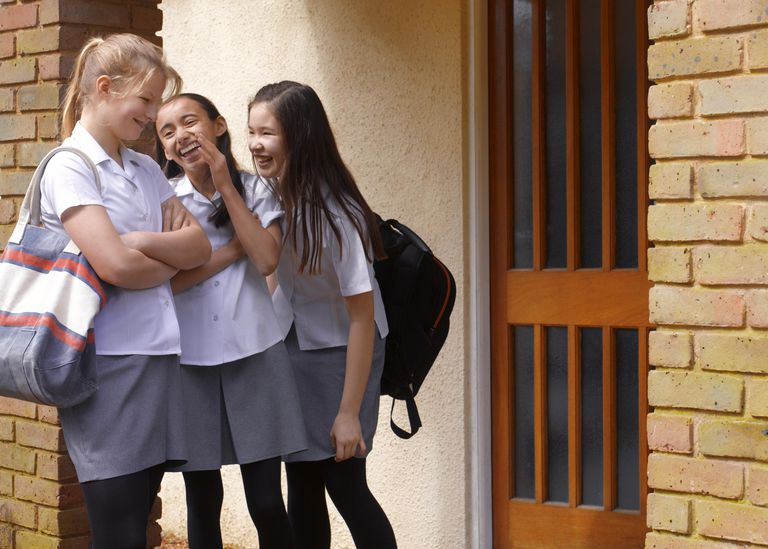School girls gossiping outside school