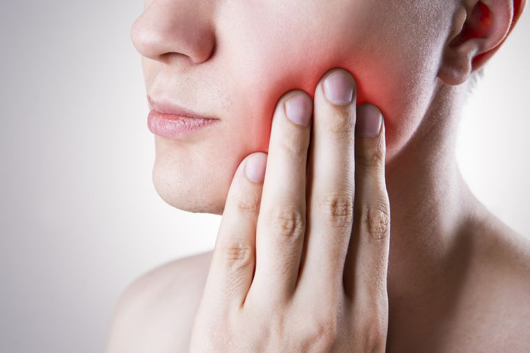 fingers on face indicating mouth pain like a cancer might cause