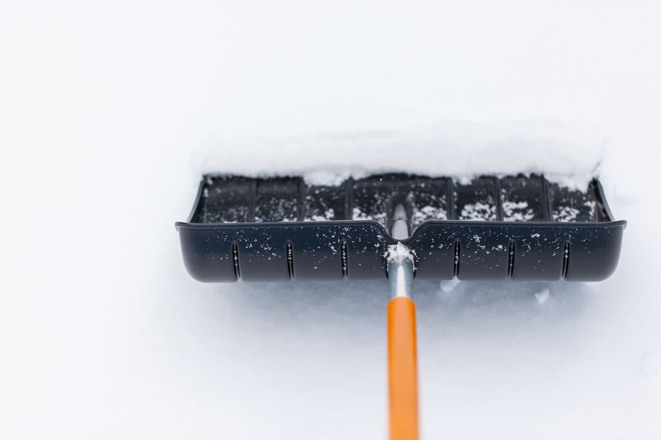 Snow shovel in snow, during snowfall. Shoveling the snow