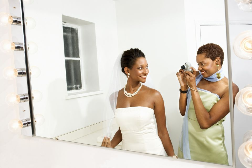 Maid of honor taking picture of bride