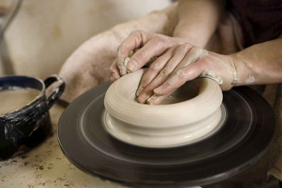 Germany, Bavaria, Mid adult woman working with clay on potter's wheel