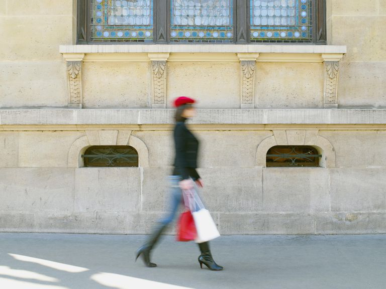 Blurred view of Caucasian woman shopping on city sidewalk