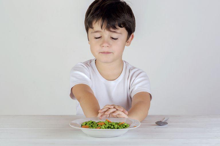 Unhappy Caucasian boy eating vegetables