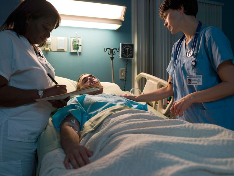 Doctor and nurse examining patient in hospital room