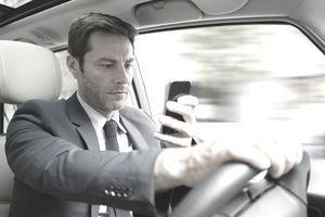 Businessman looking at smartphone while driving