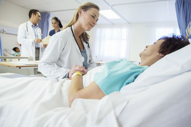 Doctor talking to woman in hospital bed