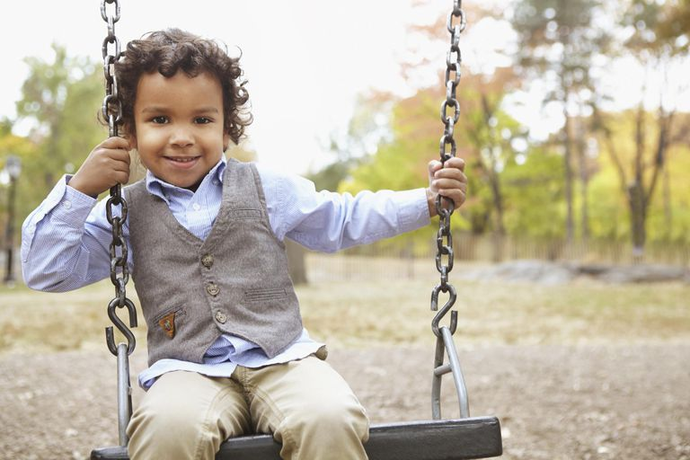 Mixed race boy sitting on swing in park