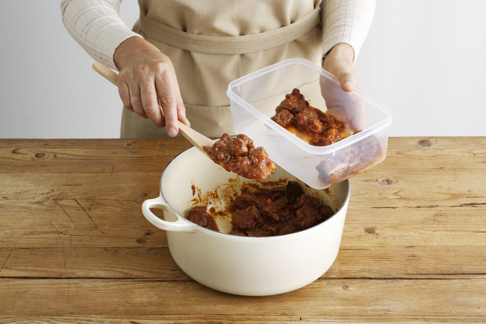 Woman spooning meat into tupperware